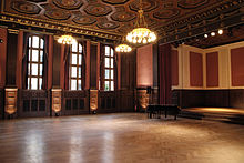 A ballroom with hardwood floors, and a ceiling decorated with chandeliers and octagon-shaped tiles. The wall on the left is decorated with dark wood panels, red walls, and windows. On the right is a small stage with a piano.