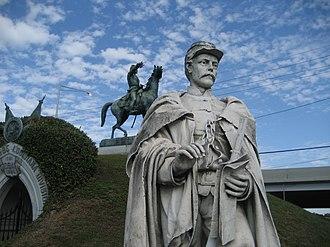 """Alexander Doyle - Doyle's """"Confederate Soldier"""" (1885); in background Doyle's equestrian statue of General Albert Sidney Johnston (1877), Metairie Cemetery, New Orleans."""