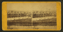 Stereo sepia views of a settlement of dozens of small buildings on a river, with water on both sides of grassy island. Both images are mounted on an oblong card yellowed with age.