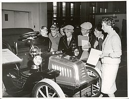"Miss M.O. Conner (right) gives a talk on a 1902 ""Peugeot"" car which is on display at the Dominion Museum, Wellington. (33499948960).jpg"