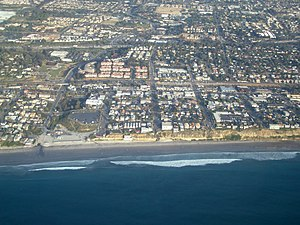 Aerial view of part of old town Encinitas showing Moonlight Beach on the left. Parallel with the shore is Historic Coast Highway 101, also parallel and further inland is Interstate 5