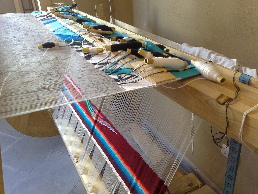 Colorful sarape in progress on a loom.