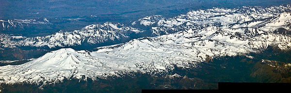 Aerial view of the Nevados de Chillan chain. Left to right: Volcan Nevado, Volcan Nuevo, Volcan Chillan. The Volcan Arrau dome complex (1973-1986) can be seen as a sharp cone-shape in front of the Volcan Nevado. Nevados de Chillan volcanic group.jpg