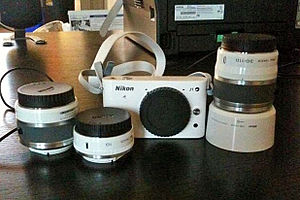 Nikon 1 series - Nikon 1 J1 with Nikkor 10-30mm f/3.5-5.6, 10mm f/2.8 pancake, and the  30-110mm f/3.8-5.6 lens in white