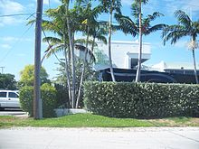White building with a hedge and palm trees in front