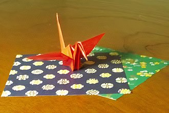 Origami - A crane and papers of the same size used to fold it