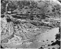 Photograph of a riverside mining operation with part of the streambed diverted for filtering and sifting for gold. A... - NARA - 296579.tif
