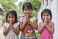 Portrait photograph at bust length of three Lao girls joining their palms for the Thai greeting, front view, in Don Khon, Laos.jpg
