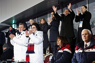 2018 North Korea–United States Singapore Summit - Moon Jae-in (standing, lower left) with the North Korean representatives (upper right) and U.S. Vice President Mike Pence (lower right) at the PyeongChang Olympics