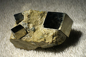Cubic crystal system - A rock containing three crystals of pyrite (FeS2). The crystal structure of pyrite is primitive cubic, and this is reflected in the cubic symmetry of its natural crystal facets.