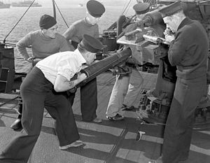 Defensively equipped merchant ship - The gun crew of a defensively equipped merchant ship during a drill at Halifax, Nova Scotia in 1942. A merchant seaman is passing a shell to the Royal Navy gunners.