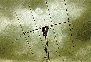 Quad antenna - A 4-element amateur radio quad antenna. The two men working on it show the scale.  The wire loops are almost invisible, suspended on the ends of the crossed supports.