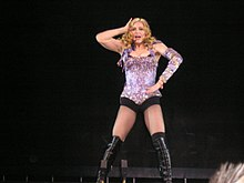 Image of a blonde woman. She is wearing a purple sparkling corset with black shorts and black knee-high boots. She has her right arm to her hip and her left arm to her head.