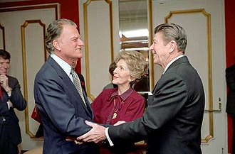 Billy Graham - President Ronald Reagan and first lady Nancy Reagan greet Graham at the National Prayer Breakfast of 1981