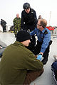 Royal Canadian Air Force Capt. Ryan McCallum, right, a medical officer, updates a member of the Royal Canadian Mounted Police on a simulated casualty's status after boarding the survey research vessel Strait 120508-N-IL267-059.jpg