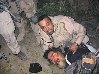 Special mission unit - An Iraqi-American military interpreter pictured with Saddam shortly after his capture.