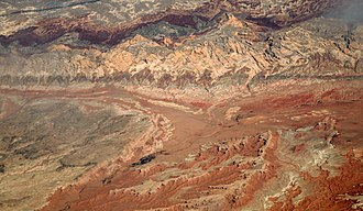 San Rafael Swell - Aerial view of San Rafael Desert. Goblin Valley is at lower extreme right, with Wild Horse Butte to the left. The shadow of a contrail marks the San Rafael Reef, with the Swell behind it.