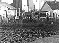 Setting av poteter på Vallø Oljeraffineri - Arbeidere spar opp jorde ved hovedport.jpg