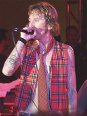 A man wearing an unbuttoned vest and a red tie holds a microphone to his face.