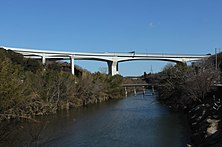 豊田東JCTに接続する豊田巴川橋[241]。コスト縮減の一環として採用されている鋼とコンクリートの複合構造。上部工の両側が波打っているのは鋼(波形鋼板)である。これにより全てをコンクリート製とする場合と比べて重量が軽減される。その結果として基礎や橋脚の負担が軽減することで下部構造を縮小してコスト低減につながり[242]、併せて工期も短縮できることで、この点でも建設費の圧縮に貢献している[242]。この波形鋼板ウエブPC箱桁橋は、2000年代に入って以降は高速道路の橋梁では標準的な構造となり、新東名でも複数採用されている[243]。
