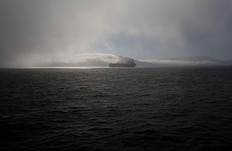 Ship passes through a light patch amid dark fog on the San Francisco Bay