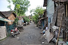 An unpaved road with huts on two sides in a slum area
