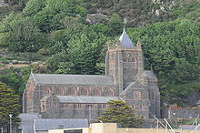 A large church standing before a hillside, with a clerestory and, to the left a tower with a pyramidal roof.