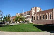 Un largo edificio escolar de ladrillo de tres pisos en la cima de una colina.
