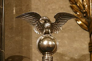Mace of the United States House of Representatives - Sitting above the ebony rods of the mace is a cast-silver globe, which holds an eagle with spread wings. The continents are etched into the globe, with North America facing front. The eagle, the national bird, is cast in solid silver.
