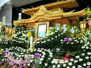 Japanese funeral - Funeral arrangement, with flower arrangements, a portrait of the deceased, and an ihai, a spirit tablet. For privacy reasons, the name of the dead person, as well as the face on the portrait are censored out via pixellation.