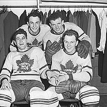Ice hockey players in a locker room. Two are sitting on a locker room bench, with another two players standing behind them.