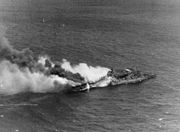USS Santa Fe (CL-60) fighting fires aboard the burning USS Franklin (CV-13) on 19 March 1945 (80-G-373734)