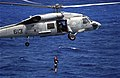 "US Navy 010904-N-0295M-004 A SH-60F Seahawk assigned to the ""Golden Falcons"" of Helicopter Anti-Submarine Squadron Two (HS-2) demonstrates the lowering of a Search and Rescue (SAR) swimmer.jpg"
