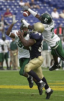 US Navy 030920-N-9693M-002 Eastern Michigan University (EMU) defenders, Jerry Gaines, left, and Yves Dieudonne, right, block a pass intended for Navy slot back Eric Roberts.jpg