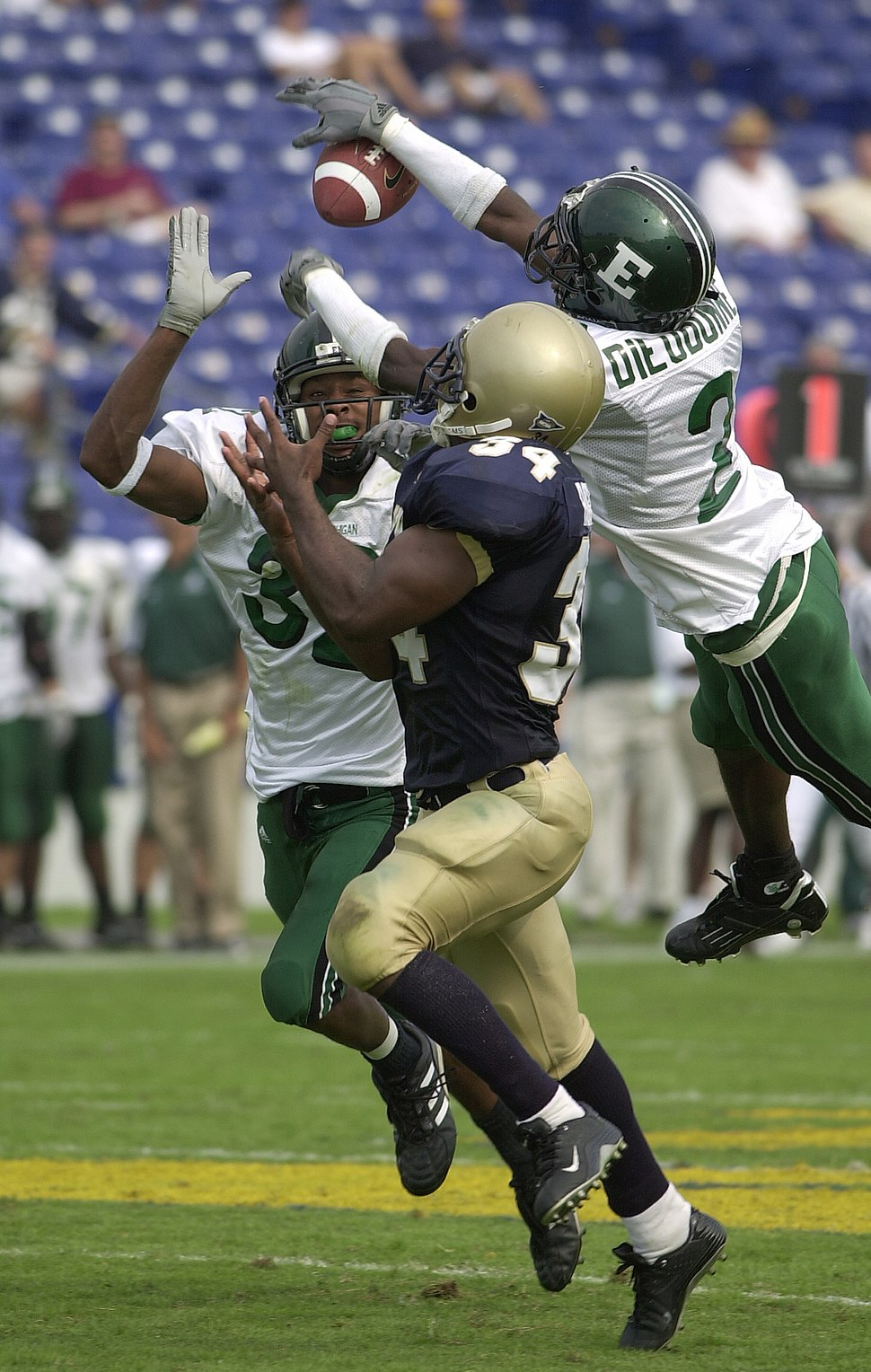 US Navy 030920-N-9693M-002 Eastern Michigan University (EMU) defenders, Jerry Gaines, left, and Yves Dieudonne, right, block a pass intended for Navy slot back Eric Roberts