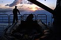 US Navy 040709-N-6932B-042 A sailor assigned to Naval Special Clearing Team One (NSCT 1), on board High-Speed Vessel Swift (HSV 2), watches the setting sun prior to a night-time clandestine mine sweep training exercise.jpg
