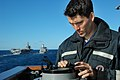US Navy 050624-N-5781F-034 Quartermaster 2nd Class Nicholas Pavlow consults an azimuth circle aboard the guided missile cruiser USS Cowpens (CG 63) to find bearing and range before conducting a replenishment at sea (RAS).jpg