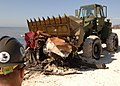 US Navy 060302-N-9246W-011 Equipment Operator 3rd Class Paul Johnson, assigned to Naval Mobile Construction Battalion Seven Four (NMCB-74) uses a front end loader to move piles of debris collected from the Gulf of Mexico shorel.jpg