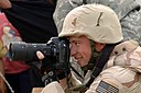 US Navy 060428-N-2911P-014 U.S. Navy Photographer's Mate 1st Class Bart Bauer assigned to Fleet Combat Camera Group Pacific, photographs U.S. Army Soldiers from the Dark Knights of Delta Company (cropped).jpg