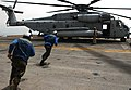 US Navy 060430-N-9866B-010 Flight deck personnel run toward a CH-53Super Stallion helicopter to remove the chalks and chains before it takes off from the flight deck.jpg