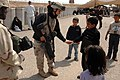 US Navy 070327-N-4928M-002 Aviation Electronics Technician 3rd Class Shannan Foley, assigned to the Navy Provisional Detainee Battalion, plays with an Iraqi child as he waits at the Camp Bucca Visitors Center to see a relative.jpg