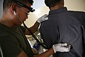 US Navy 070614-M-6412C-011 A Navy corpsman with the Police Transition Team, Regimental Combat Team 6, examines an Iraqi man that is applying for the Iraqi police at the new Iraqi police station.jpg