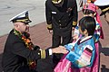 US Navy 081008-N-9123L-004 Cmdr. John S. Banigan, commanding officer of the guided-missile destroyer USS John S. McCain (DDG 56), gives a Korean child a ship's coin after receiving a traditional flower wreath presented to welco.jpg