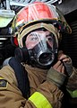 US Navy 081113-N-9758L-034 A Sailor assigned to the Pearl Harbor-based Arleigh Burke-class guided-missile destroyer USS Paul Hamilton (DDG 60) dons a fire-fighting helmet during a fire drill in the ship's personnel office.jpg