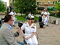"US Navy 090612-N-2888Q-034 Navy Recruiting Command (CNRC) Deputy Commander Rear Adm. Robin Braun is interviewed by Doug Warner, host of the KWTV News 9 Morning Show, while U.S. Navy Band Mid South ""Freedom"".jpg"