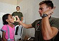 US Navy 091019-M-7747B-001 Lt. Brandon Van Noord, from Lansing, Mich., assigned to the 11th Marine Expeditionary Unit shows a girl how to use an inhaler.jpg