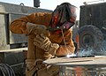 US Navy 091031-N-9564W-041 Steelworker Constructionman Tanner Casto uses an arc welder to make a triceps pull-down bar for the Camp Natasha gym.jpg