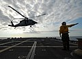 US Navy 100224-N-7058E-138 Aviation Electrician's Mate 3rd Class David Harden launches a MH-60S Sea Hawk helicopter assigned to Helicopter Sea Combat Squadron (HSC) 22 from the littoral combat ship USS Freedom (LCS 1).jpg