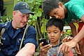 US Navy 110506-N-SP676-176 Mineman 3rd Class Matt Miller gives children his smart phone to play with at the Bukit Harapan home for disabled and dis.jpg