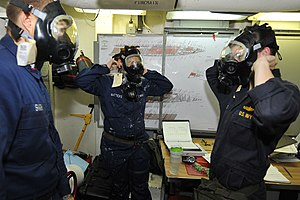 US Navy 111230-N-KS651-302 Sailors aboard the amphibious dock landing ship USS Pearl Harbor (LSD 52) don their gas masks during a general quarters.jpg